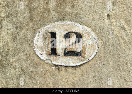 Painted number Twelve on a stone wall - Stock Photo