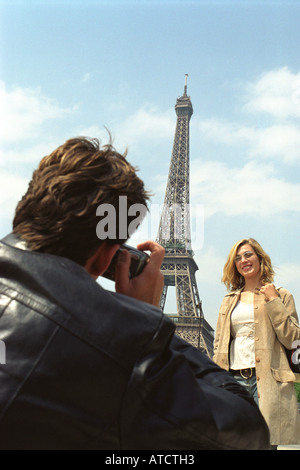 Man taking photographs of woman in front of Eiffel Tower, Paris, France - Stock Photo