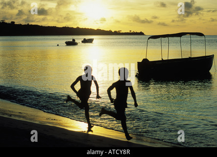 Boys run at 2 Mile Crescent  beach in Grand Anse  Grenada - Stock Photo