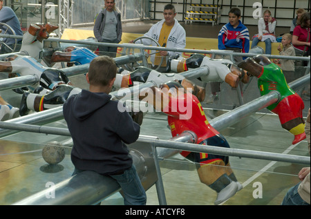 A boy watching a football match at the oversized table soccer in Neue Kranzler Eck. Charlottenburg, Berlin, 2005. - Stock Photo