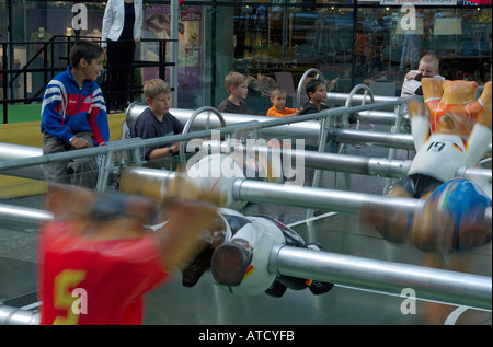 Boys playing football at the oversized table soccer in Neue Kranzler Eck. Charlottenburg, Berlin, 2005. - Stock Photo