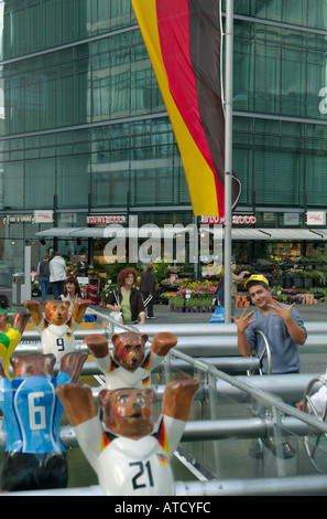 Boys playing football at the oversized table soccer in Neue Kranzler Eck. German flag in background. Charlottenburg, - Stock Photo