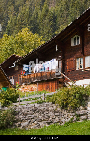 Swiss chalet with laundry hanging from clothesline on deck under wide roof eaves in the village of Gimmelwald Switzerland - Stock Photo