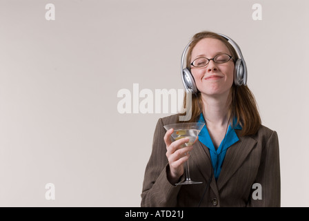 a young business woman relaxes with a martini and music after work - Stock Photo