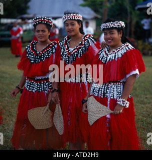 Three female dancers wearing costumes of red and white decorated with shells from the Wallis Islands in the South - Stock Photo