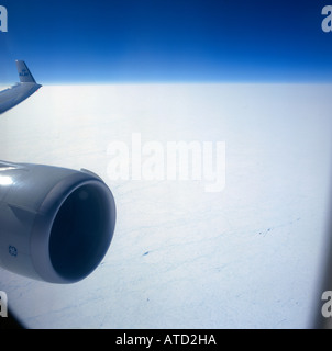 Aerial view of the Canadian Arctic region from window of an airliner with sunlit engine intake and wing tip on left - Stock Photo