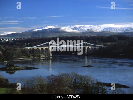 Menai Suspension Bridge Snowdonia in snow in background Anglesey North Wales UK - Stock Photo
