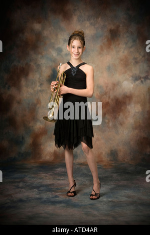 [full body] length portrait of happy young teenage girl holding trumpet with smile - Stock Photo