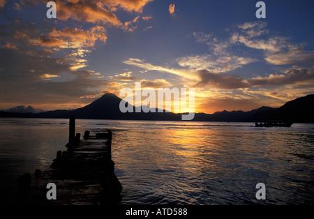Boats and jetty Silhouetted at sunset Panajachel Lake Atitlan Guatemala San Pedro volcano beyond - Stock Photo
