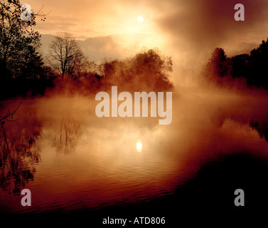 Mist rises off of Beaver dam Lake in Asheville North Carolina at dawn with the Blue Ridge mountains in the background - Stock Photo