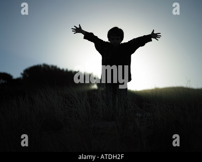 boy with arms out wide boy standing on ridge with light streaming in from behind with arms out wide and fingers - Stock Photo