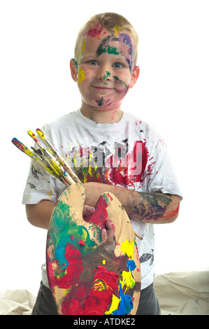 Six year old boy stands poudly with painter's palette and brushes.