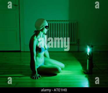 Swimmer sitting in front of tanning lamp - Stock Photo