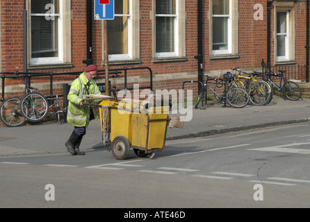 Street cleaner and yellow dust cart in the Cowley Road Oxford - Stock Photo