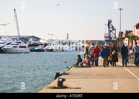 People enjoying early Spring sunshine on Poole Quay. Opposite is the Sunseeker boat factory. Dorset. UK. - Stock Photo