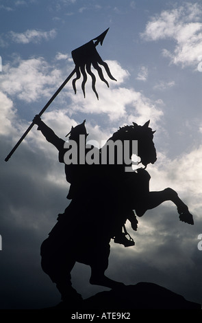A statue of William the Conqueror which stands in a triumphant pose by the Hotel de Ville Set as a silhouette against - Stock Photo