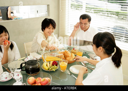 Parents and their two daughters having breakfast - Stock Photo