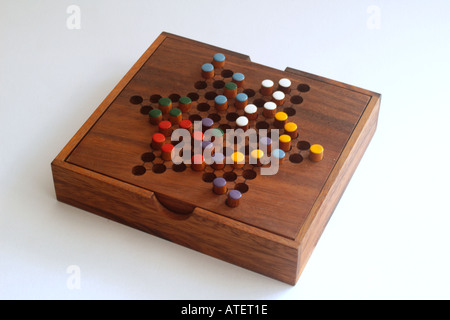 Chinese checkers colour pegs on a wooden board A game of strategy and planning - Stock Photo