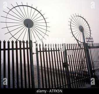 Galvanized gates with circular anti climb spikes London England UK - Stock Photo