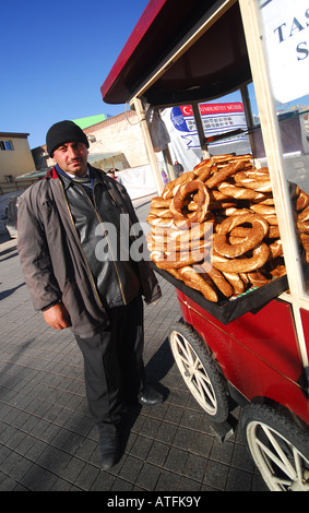 ISTANBUL, TURKEY. Man selling simits (sesame-coated pretzel breads) on Taksim Square at the end of Istiklal Caddesi. - Stock Photo