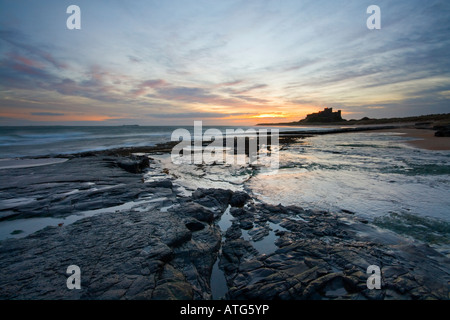 Sunrise on the deserted beach at Bamburgh with the castle in the distance Northumberland - Stock Photo