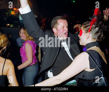 A smartly dressed man in suit and bow tie dances with a woman in a red mask - Stock Photo