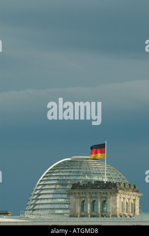 German flag and new cupola by Sir Norman Foster on the old Reichstag building in Berlin's government district. Berlin - Stock Photo