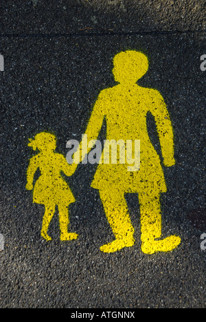 a painted yellow sign on a wet road of a child holding her mothers hand. - Stock Photo