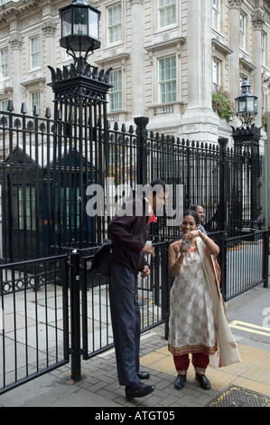 Tourists taking pictures of each other outside the security gates at the entrance to Downing Street London - Stock Photo