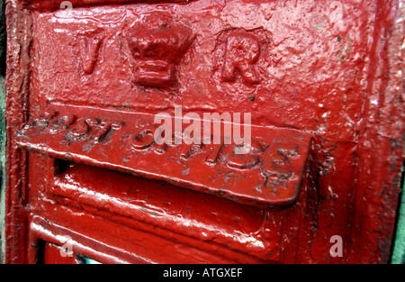 Close up of a Victorian letterbox with battered thick red paint. - Stock Photo