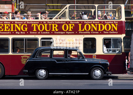 Black cab parked alongside the Sightseeing Tour of London open top bus - Stock Photo