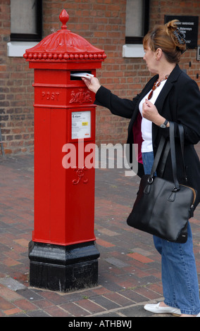 Woman posting letter in Victorian post box in Gloucester Docks England Uk - Stock Photo