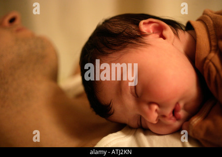 Baby girl asleep on her father's chest - Stock Photo
