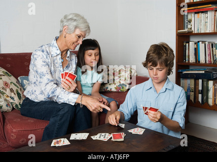 grandmother playing cards with grandchildren - Stock Photo