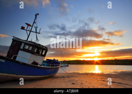 Old fishing boat moored in Alnmouth estruary at low tide and backed by a sunset sky - Stock Photo