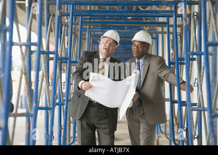 Two engineers discussing at a construction site - Stock Photo