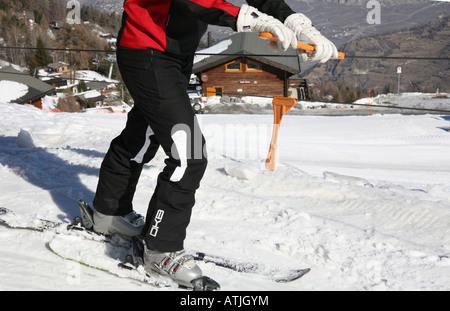 Skier getting on drag ski lift at La Tzoumaz Switzerland - Stock Photo