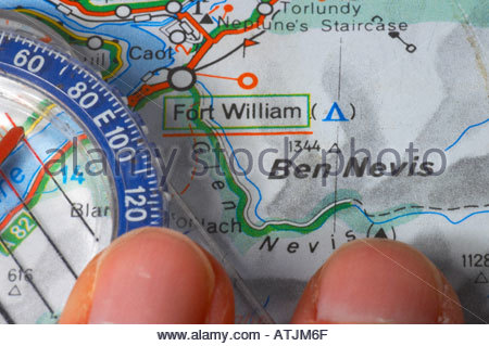 Someone pointing at a map of Ben Nevis and a compass - Stock Photo