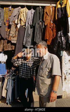 Shop keeper and customer standing in front of clothes shop. Beirut, Lebanon. - Stock Photo