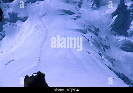Climbers descending the route from Mont Blanc summit in the French alps towards the Aiguille du Midi - Stock Photo