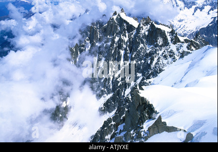 Aiguilles north west of Aiguille du Midi appearing through clouds, French alps - Stock Photo