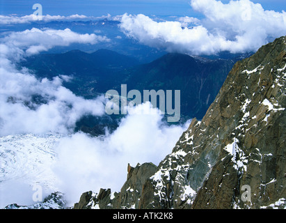 view from the Aiguille du Midi towards Chamonix through puffy clouds, French alps - Stock Photo