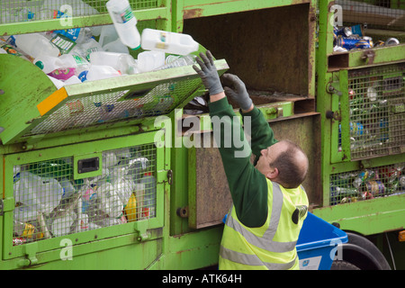 Council recycling service workman sorting plastic bottles of household rubbish into green lorry for recycling North - Stock Photo