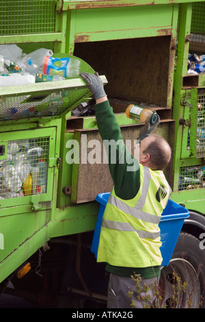 Council recycling service workman sorting plastic bottles of household rubbish into green lorry for recycling part - Stock Photo