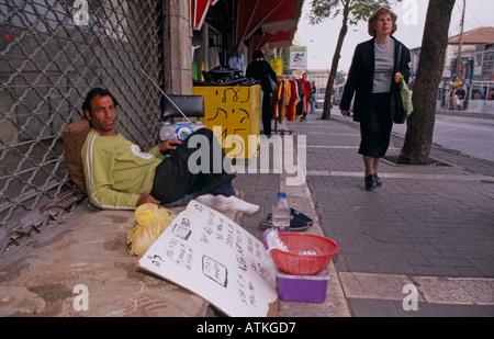 Homeless man sits on pavement, Jerusalem - Stock Photo