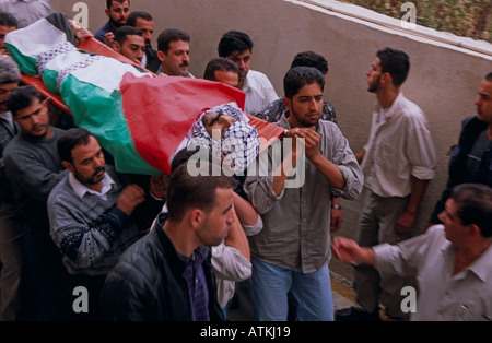 People carrying a body of a man wrapped in Palestine Flag - Stock Photo