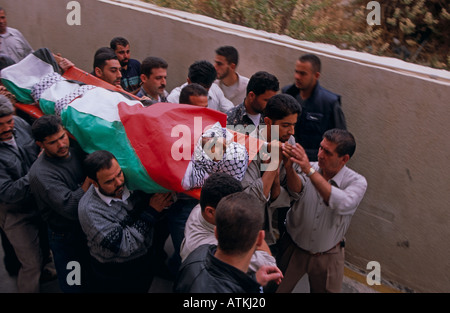Men carrying a body wrapped in Palestine flag - Stock Photo
