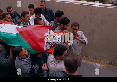 A group of men carrying a body wrapped in Palestine flag - Stock Photo