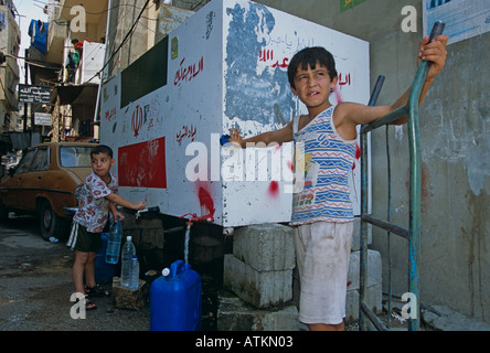 Children filling water from tank, Shatila Palestinian refugee camp, Beirut, Lebanon - Stock Photo