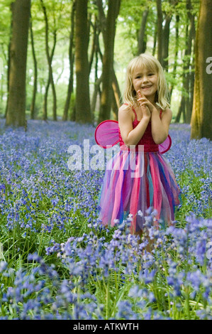 A five year old girl dressed in a fairy outfit in an English bluebell wood. - Stock Photo
